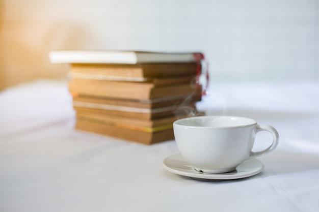 一杯のコーヒーとベッドの上の本。本の上にコーヒーを飲みながら白いカップ。閉じる Premium写真