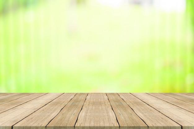 あなたの製品をモンタージュのための自然の緑の背景をぼかした写真の上の木のテーブルトップ Premium写真