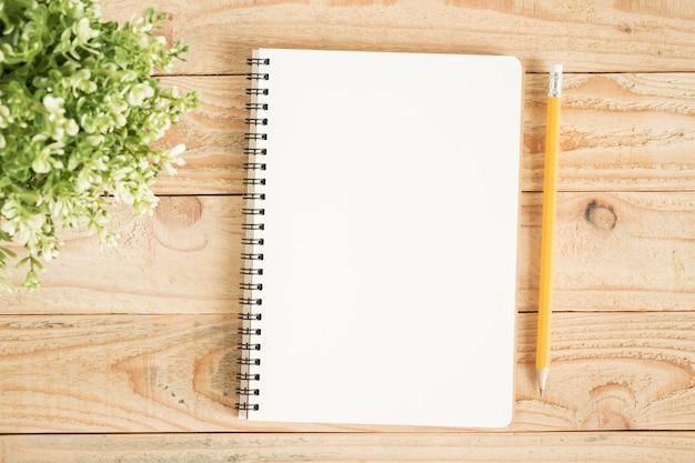 空白のノートブックと茶色の木の上の黄色の鉛筆 Premium写真