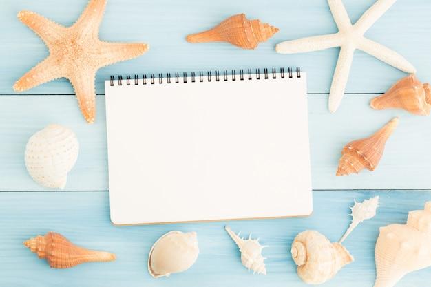 空白のノートブックと青い木製の床の貝殻。 Premium写真