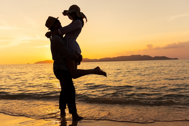 Азиатские пары выражая свои чувства, стоя на пляже, молодые пары обнимаются на море на закате Premium Фотографии