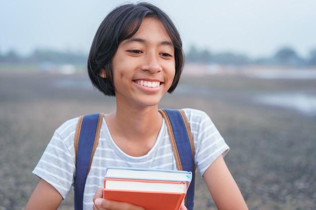 幸せなアジアの女の子の顔に笑顔し、立っている間笑う朝の自然の中で、アジアの子供は本とバックパックを保持します Premium写真