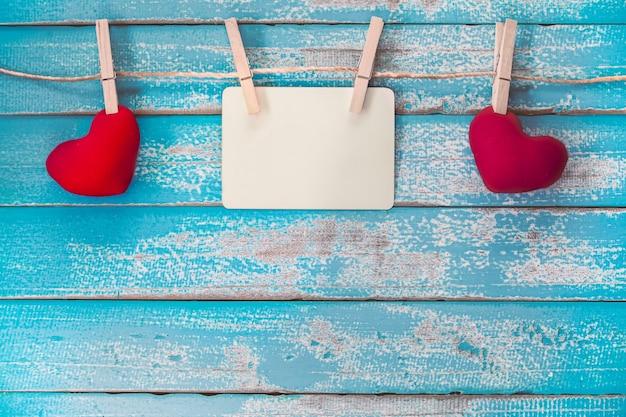 空のフォトフレームのアルバムと赤い心は、ヴィンテージ青い木の背景にぶら下がって Premium写真