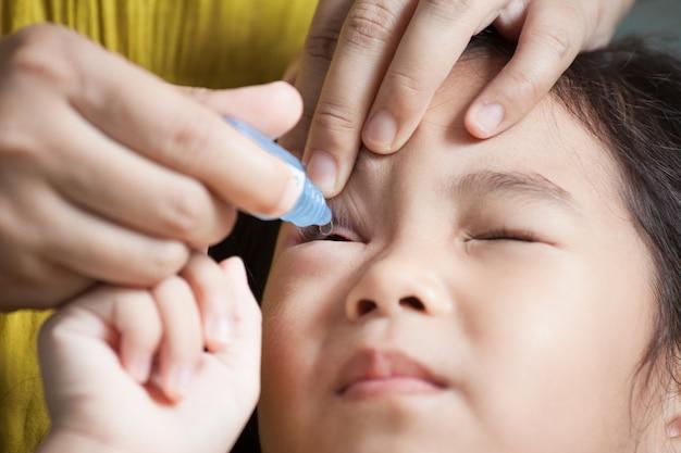 子供の目に眼薬を滴下する母親 Premium写真