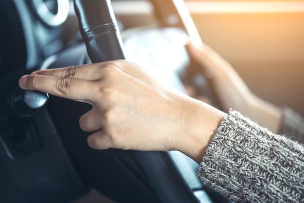 車の運転中に車の雨のフロントガラスのワイパーコントロールスティックを制御する女性の手 Premium写真