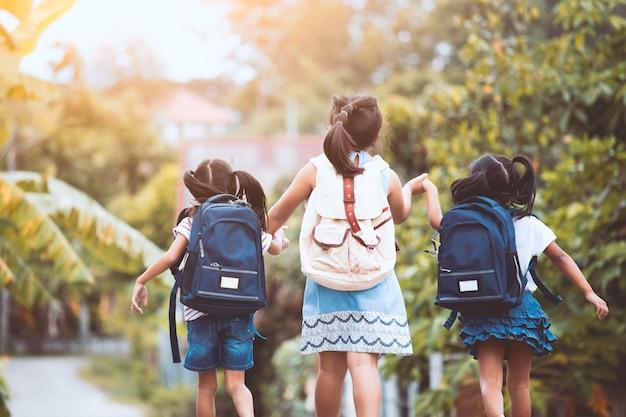 学校に戻る。一緒に学校に行くバックパックとアジアの瞳の子供たち Premium写真