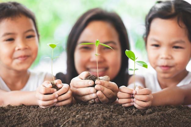 幸せな家族の母親と娘は、植えのために手に若い木を保持するのが楽しい Premium写真