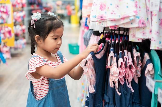 かわいいアジアの子供の女の子がスーパーマーケットの服部門でドレスを選ぶ Premium写真