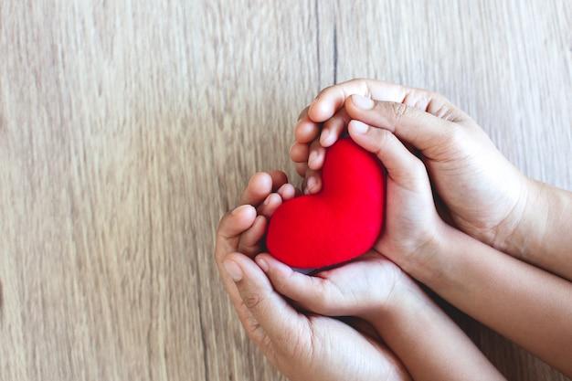 愛と調和を持つ木製のテーブル背景に子供の手と親の手で赤いハート Premium写真