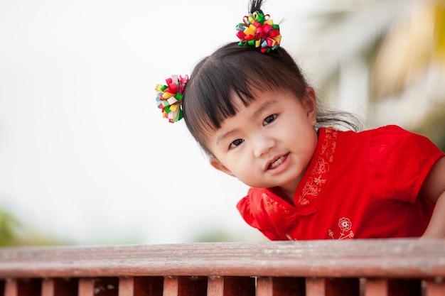 中国の伝統的なドレスで幸せなかわいいアジア小さな子供女の子笑顔 Premium写真