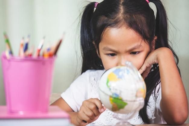 かわいいアジアの子供の女の子は教室で地球を見て、勉強するために拡大鏡を使う Premium写真