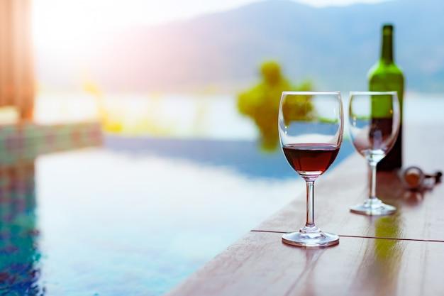 Два бокала красного вина возле бассейна с потрясающим видом на море Premium Фотографии