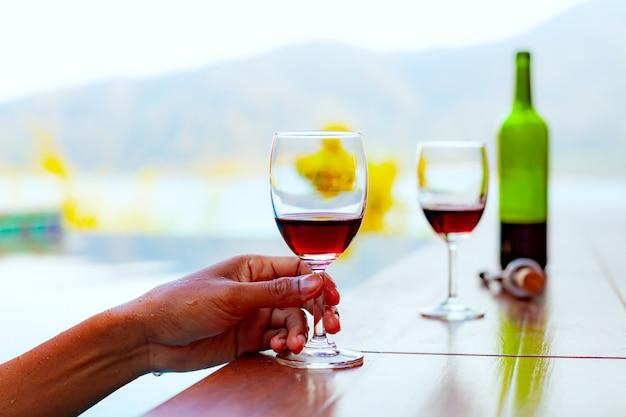 男は水泳やプールでリラックスしながら赤ワインを飲む Premium写真