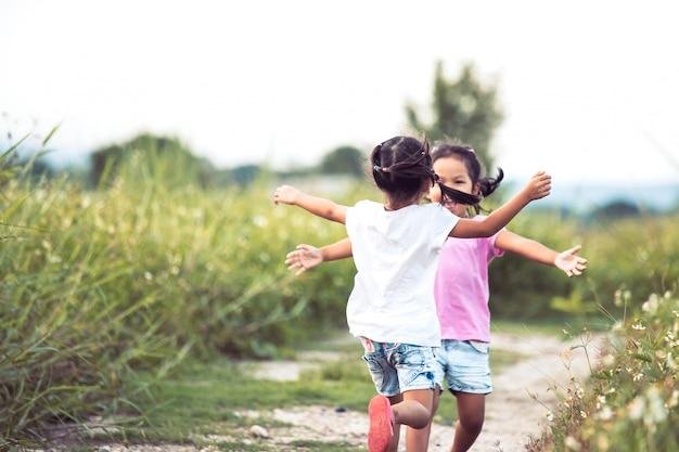 Две азиатские девчонки бегают обнимать друг друга в винтажном цвете Premium Фотографии