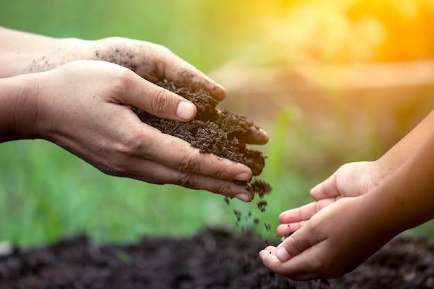 ビンテージの色調で一緒に植えるために子供に土を与える母の手 Premium写真