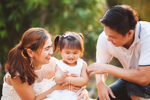 アジア家族父母と娘が公園で愛と幸せを一緒に遊んで Premium写真