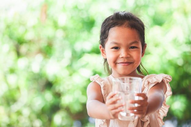 アジアのかわいい子女の子水を飲むのが好きで、新鮮な水のガラスを保持 Premium写真