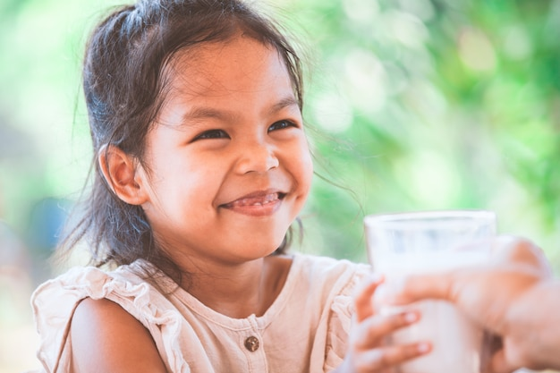 Милая азиатская девушка ребенка усмехаясь когда получает стакан молока от ее матери Premium Фотографии
