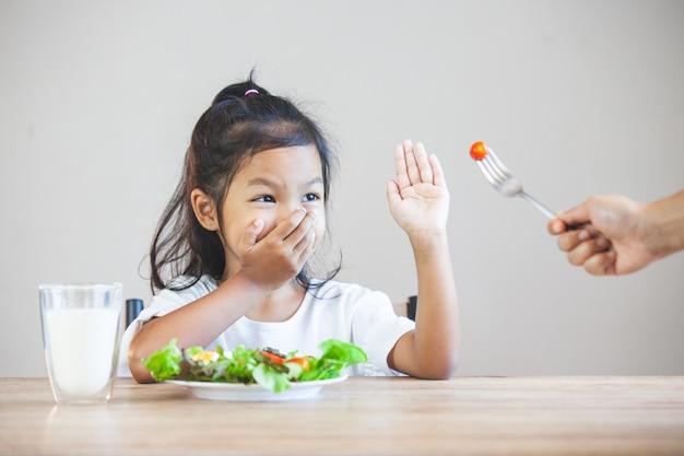 アジアの子供は野菜を食べるのが好きではなく、健康的な野菜を食べることを拒否します Premium写真