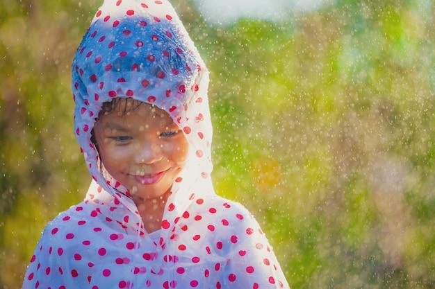 日光の下で雨と遊ぶことを楽しんでレインコートを着て幸せなアジア子供女の子 Premium写真