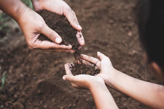 子と親が土を持って一緒に植樹するための土を準備 Premium写真