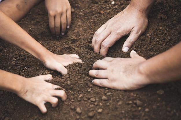 土を掘る子どもと親が一緒に木を植える準備をする Premium写真