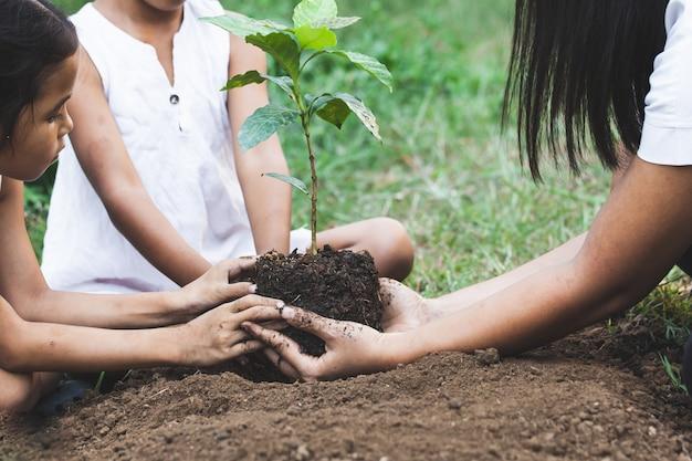 子供と親の手が一緒に黒い土に若い木を植える Premium写真