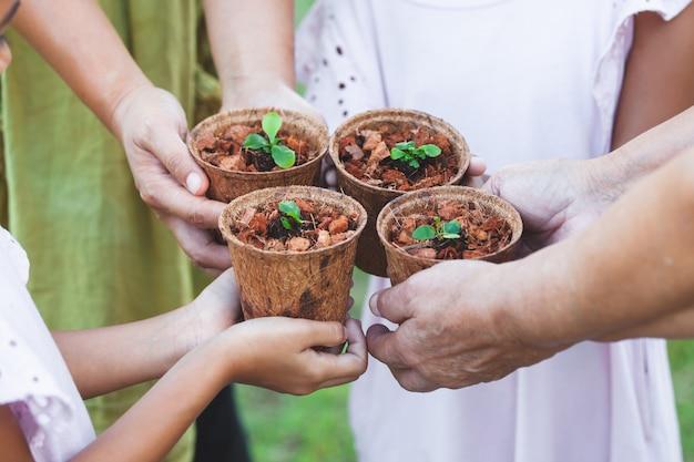 リサイクルファイバーポットで若い苗を一緒に保持している子供と親の手 Premium写真