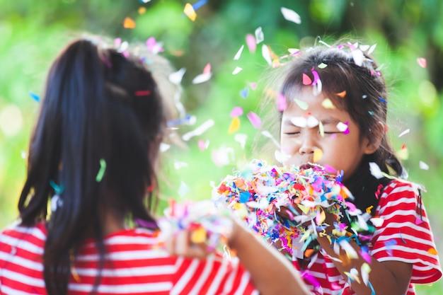 かわいいアジアの子供の女の子と彼女の妹は、パーティーで祝うために一緒にカラフルな紙吹雪で遊ぶ Premium写真