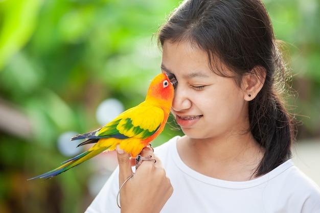Красивые птицы попугая стоя на руке женщины. азиатская девушка-подросток играет со своей птицей-попугаем Premium Фотографии