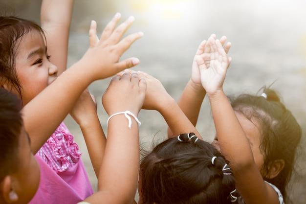 Дети поднимают руки и играют вместе в парке в старинном цветовом тоне Premium Фотографии