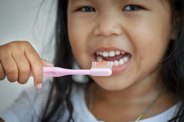 彼女の歯を磨くアジアの少女。閉じる Premium写真