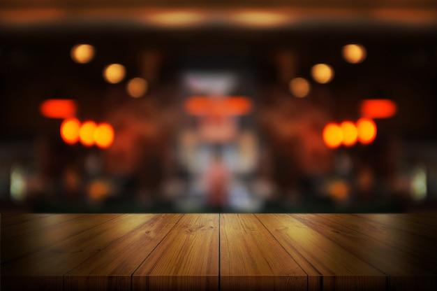 ぼやけているコーヒーショップと空の木製テーブルトップ。 Premium写真