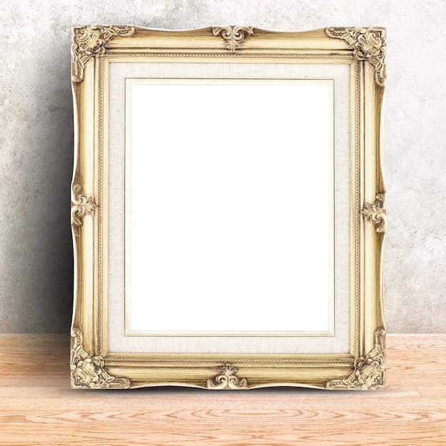 コンクリートの壁や木製のテーブルでゴールデンヴィンテージのフォトフレーム、製品の表示のためのテンプレートモックアップ Premium写真
