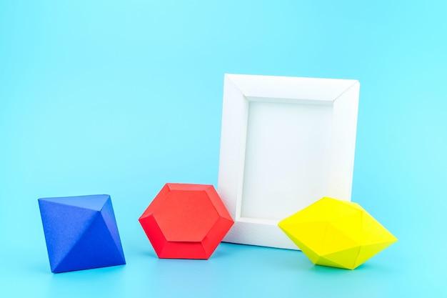 薄い青色の背景に白いフォトフレーム(紙製)とカラフルな紙の宝石 Premium写真