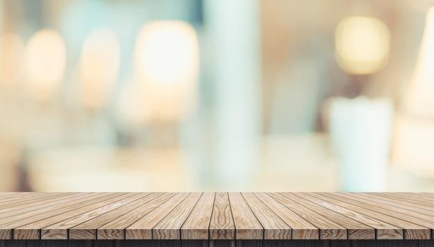 空の素朴な木の板テーブルとレストランのぼやけた柔らかいライトテーブル Premium写真