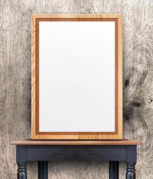 木製のテーブルの上の木製の壁で傾いている空の木製フォトフレーム Premium写真