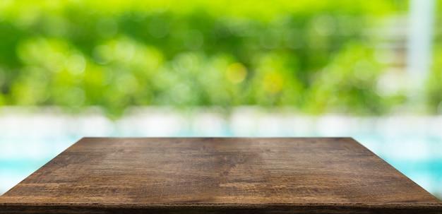 空の堅い木のテーブルとぼやけたヘッジとプール Premium写真