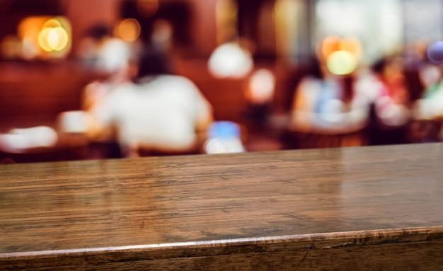 レストランでの人々の夕食の木のテーブルぼかしの背景 Premium写真