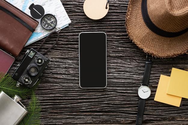 トップビュー携帯電話や探検家もの古い木製の机の上のアイテムと一緒に旅行。 Premium写真