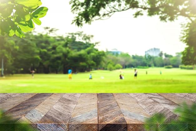 ぼかし公園緑自然ボケと葉の前景を持つ空のグランジ木の板テーブルトップ Premium写真