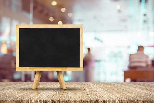 ぼかしレストランと木製のテーブルにイーゼルと黒板 Premium写真