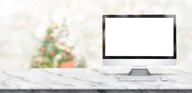 Счастливого рождества баннер, макет настольного компьютера на белом мраморном столе с размытия елки Premium Фотографии