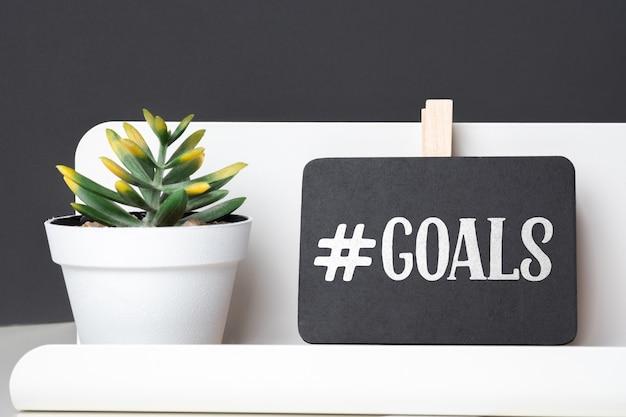 テーブルの上の白い鍋に鉛筆ボックスと緑の植物に黒板の目標 Premium写真