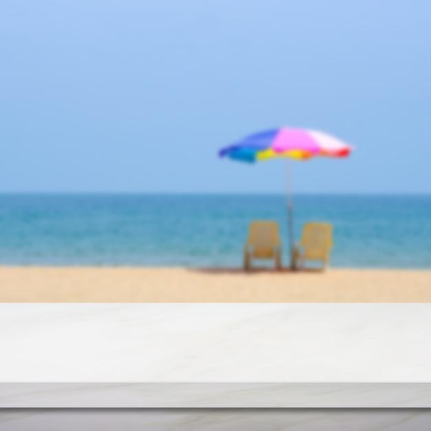 空の白い大理石のテーブルの上にカラフルな傘と青い空と海のビーチをぼかし Premium写真