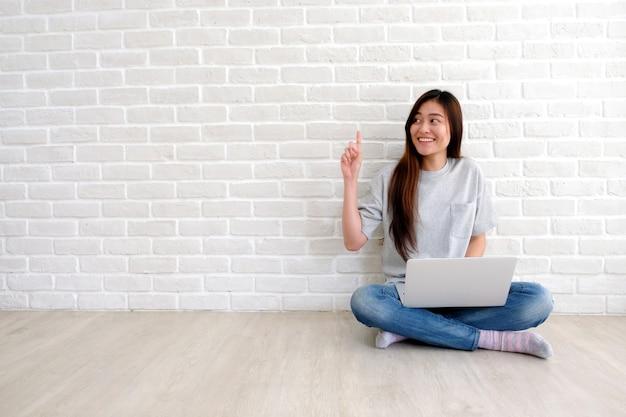 白い部屋でラップトップコンピューターを使用してカジュアルなスタイルで若いアジア女性 Premium写真