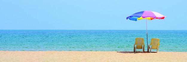 ビーチでデッキの髪とカラフルな傘 Premium写真
