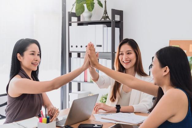 美しい幸せなアジアの女性のグループの会議とオフィススペースで一緒にハイタッチを与えることは議論やビジネススタートアッププロジェクトをブレインストーミングします。 Premium写真