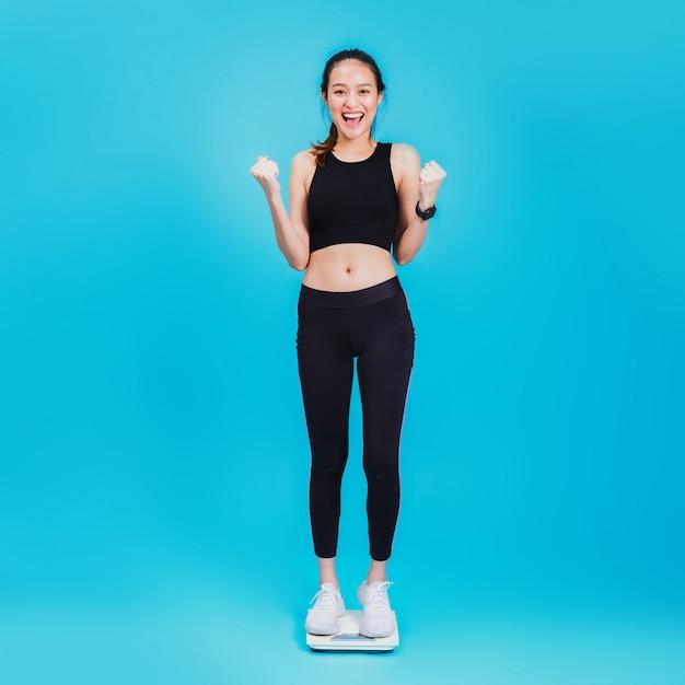 体重計の上に立って幸せと感じているアジアの美しい女性 Premium写真