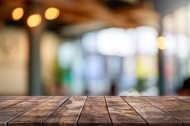 木製のテーブルトップを空にし、ガラス窓のインテリアレストランバナーをぼかして抽象的な背景を模擬-製品の表示やモンタージュに使用できます。 Premium写真